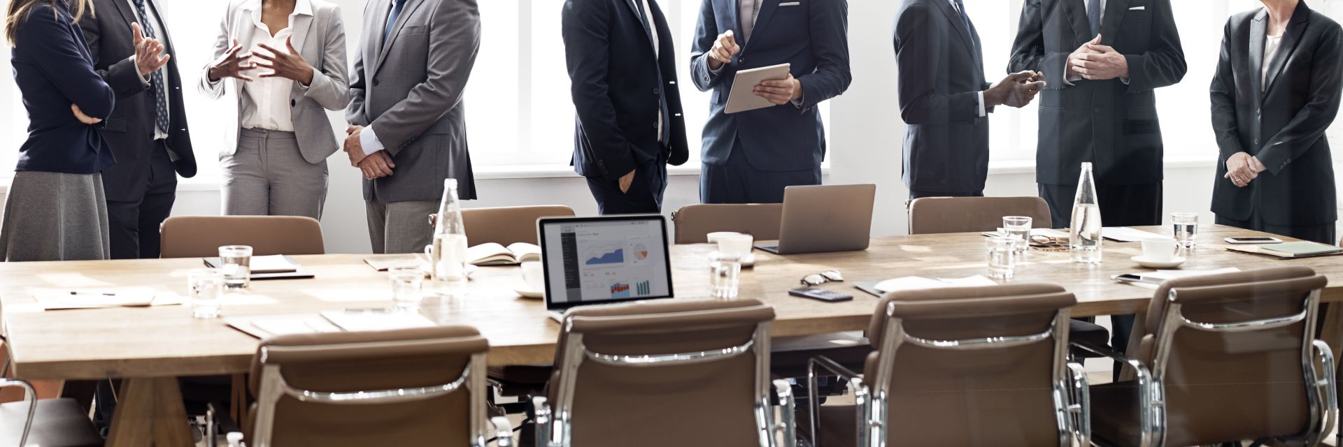 Meeting attendees having breakout discussions next to a conference table