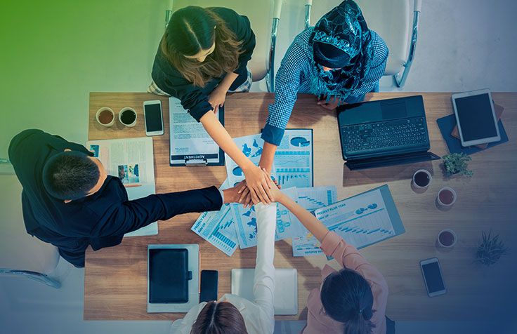 Overhead view of people around a conference table celebrating their teamwork